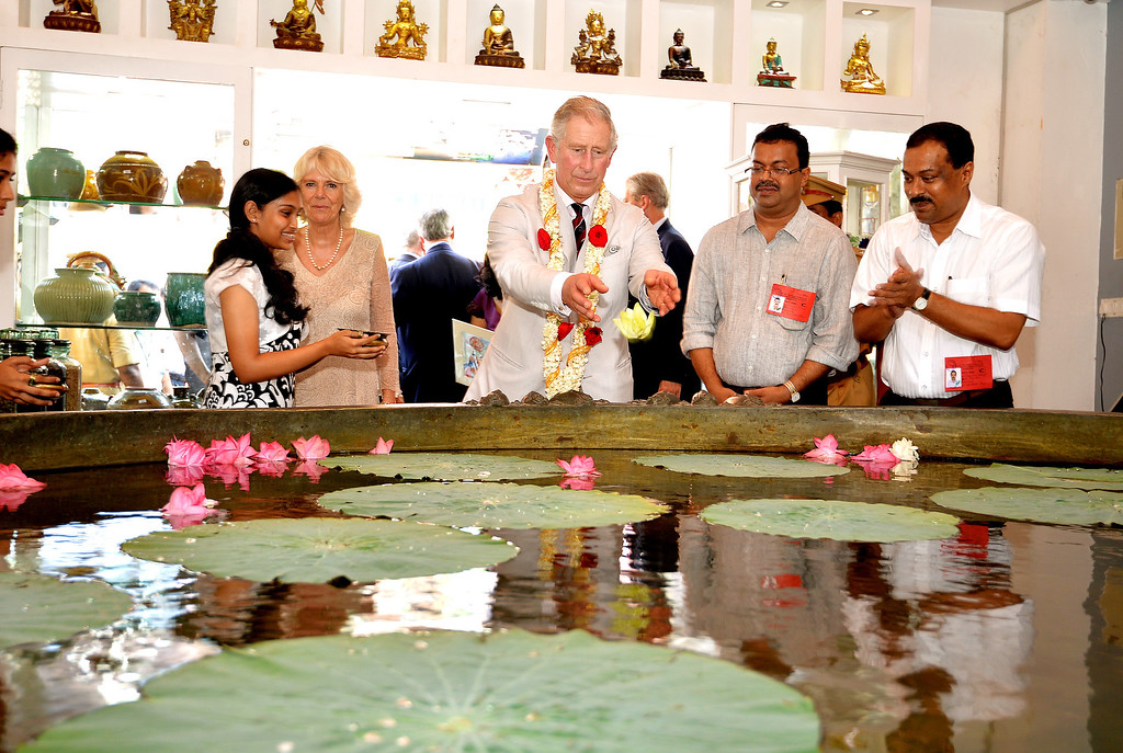 . Prince Charles, Prince of Wales throws a flower into a giant cooking bowl big enough to feed 6,000 people during a visit to Jew Street in Jew Town on day 9 of an official visit to India on November 14, 2013 in Kochi, India.   (Photo by John Stillwell - Pool/Getty Images)