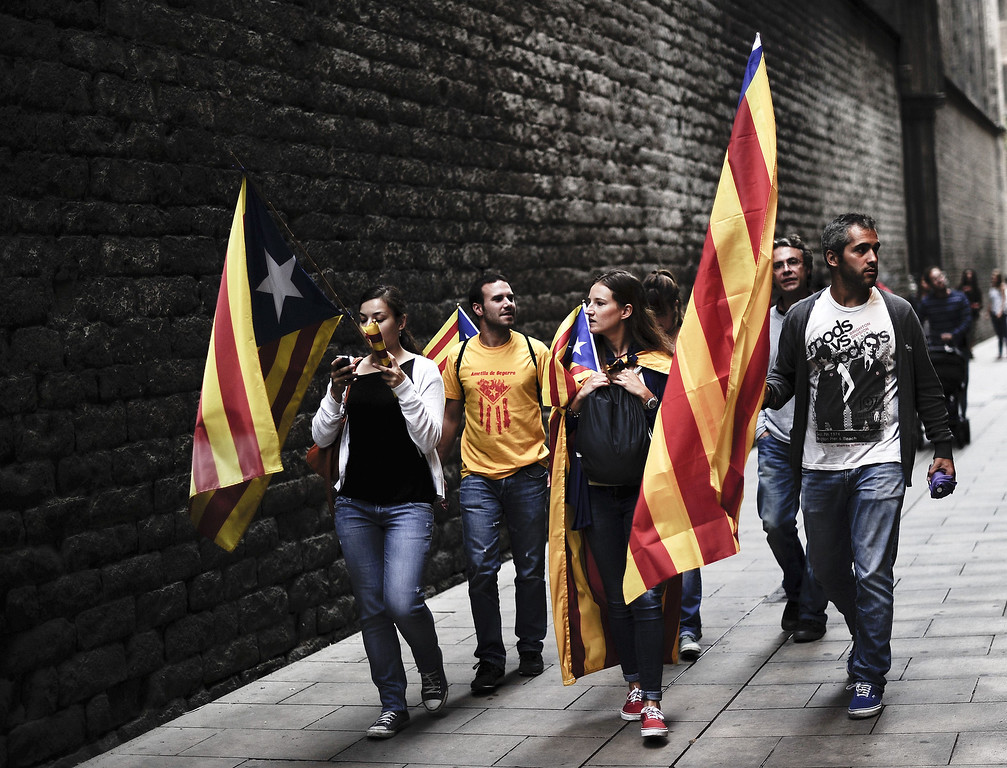 """. People carry Catalonia\'s flag \""""Estelada\"""" during celebrations for Catalonia National Day, or Diada, in Barcelona on September 11, 2013. Independence-seeking Catalans marshalled their forces today in a bid to create a 400-kilometre (250-mile) human chain they say will stretch across 86 cities, towns and villages along the coast of the northeastern region on the Mediterranean, passing landmarks such as the Sagrada Familia basilica in Barcelona and the city\'s Camp Nou football stadium. JOSEP LAGO/AFP/Getty Images"""