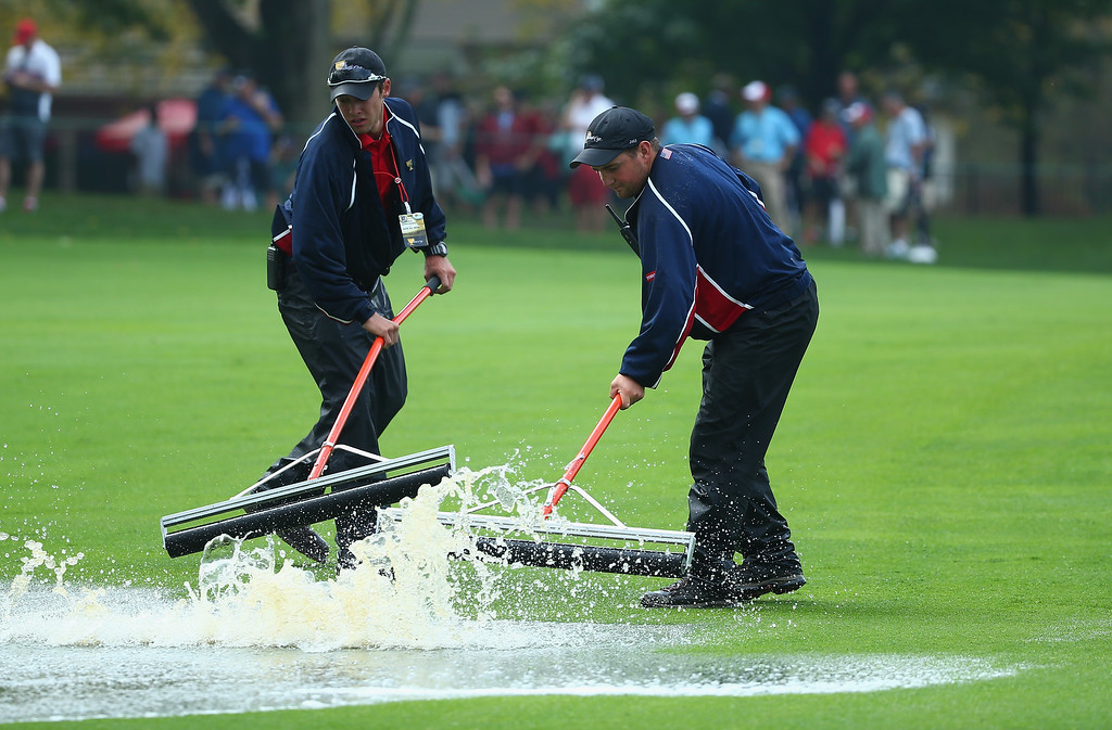 . DUBLIN, OH - OCTOBER 05:  Members of the grounds staff remove water from a fairway during a weather delay during the Day Three Four-ball Matches at the Muirfield Village Golf Club on October 5, 2013  in Dublin, Ohio.  (Photo by Andy Lyons/Getty Images)