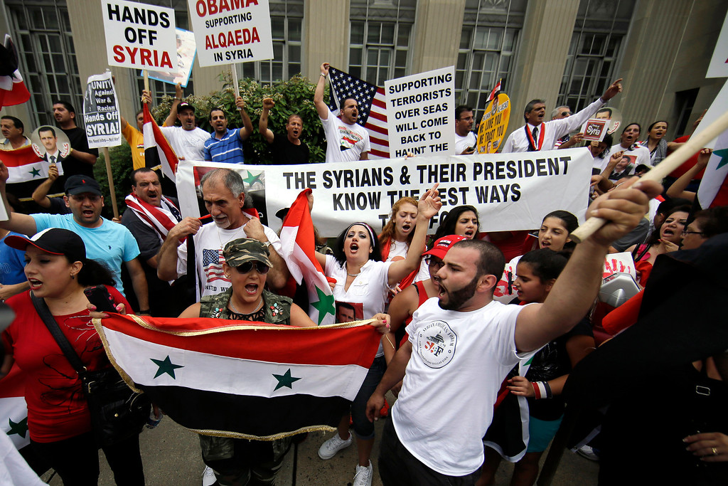 . Members of the local Syrian community cheer after marching in protest against the United States\' involvement in Syria, Friday, Aug. 30, 2013, in Allentown, Pa. President Barack Obama says he hasn\'t made a final decision about a military strike against Syria_but is considering a limited and narrow action in response to a chemical weapons attack that he says Syria\'s government carried out last week. (AP Photo/Matt Slocum)