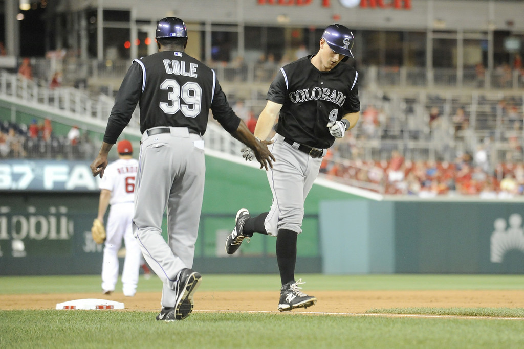 . D.J. LeMathieu #9 of the Colorado Rockies is congratulated by third base coach Stu Cole #39 on a solo home run in the eighth inning during a baseball against the Washington Nationals on July 1, 2014 at Nationals Park in Washington, DC.  The Nationals won 7-1.(Photo by Mitchell Layton/Getty Images)