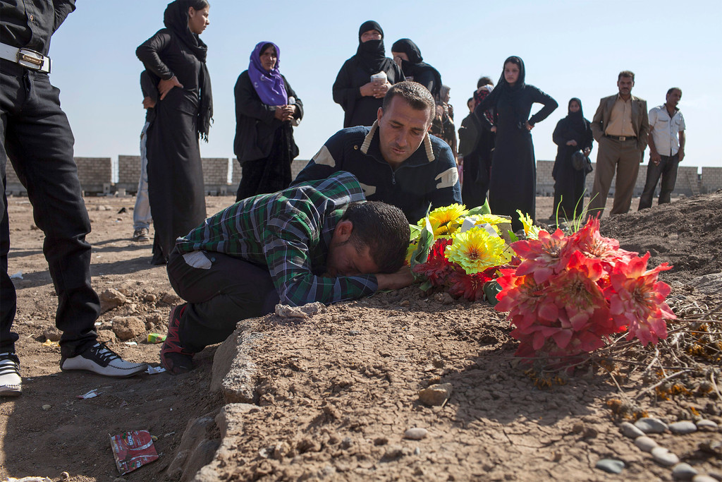 . Kurdish men grieve during a visit to the Martyrs\' cemetery to remember those who died in Syria\'s civil war on October 15, 2013, in the Syrian Kurdish town of Derik (al-Malikiyah in Arabic), on the first day of Eid al-Adha, which commemorates the willingness of Abraham to sacrifice his son at God\'s command.  AFP PHOTO/STR-/AFP/Getty Images