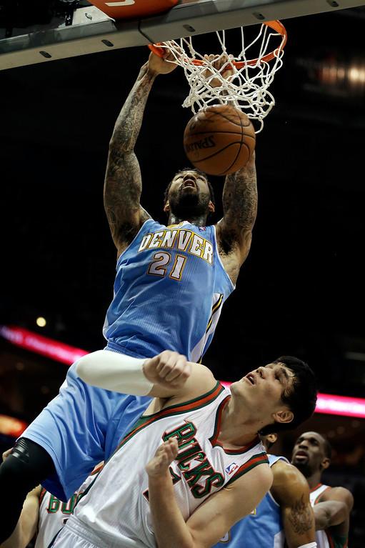 . Denver Nuggets\' Wilson Chandler (21) dunks over Milwaukee Bucks\' Ersan Ilyasova during the first half of an NBA basketball game on Monday, April 15, 2013, in Milwaukee. (AP Photo/Jeffrey Phelps)