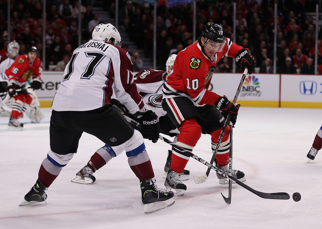 . Aaron Palushaj #17 of the Colorado Avalanche knocks the puck away from Patrick Sharp #10 of the Chicago Blackhawks at the United Center on March 6, 2013 in Chicago, Illinois.  (Photo by Jonathan Daniel/Getty Images)