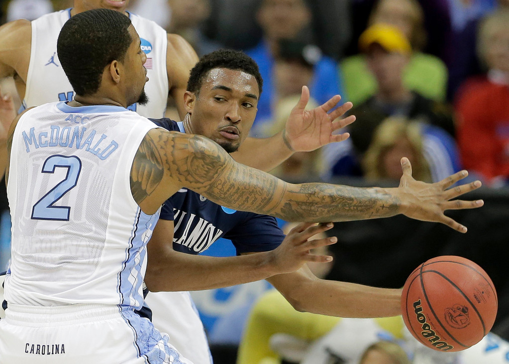 . Villanova guard Darrun Hilliard (4) passes around North Carolina guard Leslie McDonald (2) during the first half of a second-round game in the NCAA college basketball tournament Friday, March 22, 2013, in Kansas City, Mo. (AP Photo/Charlie Riedel)