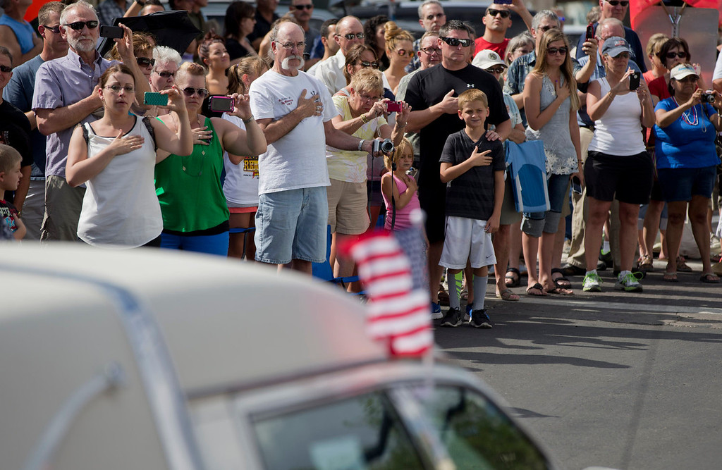 . People hold their hands over their hearts to pay their respects as 19 hearses slowly roll by, Sunday, July 7, 2013 in downtown Prescott, Ariz., carrying the 19 Granite Mountain Hotshot firefighters killed a week ago by an out-of-control blaze near Yarnell, Ariz. The nearly five-hour-long procession began near the state Capitol in Phoenix, went through the town where the Granite Mountain Hotshots were killed and ended in the mountain community of Prescott, where they lived and will be laid to rest this week.(AP Photo/Julie Jacobson)