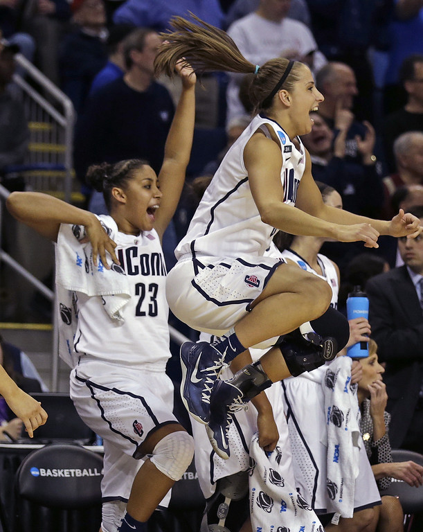 . Connecticut guard Caroline Doty, right, leaps in the air as she celebrates with teammate Kaleena Mosqueda-Lewis (23) in the final seconds of the second half of a women\'s NCAA regional final basketball game against Kentucky in Bridgeport, Conn., Monday, April 1, 2013. Connecticut won 83-53 and advances to the Final Four. (AP Photo/Charles Krupa)