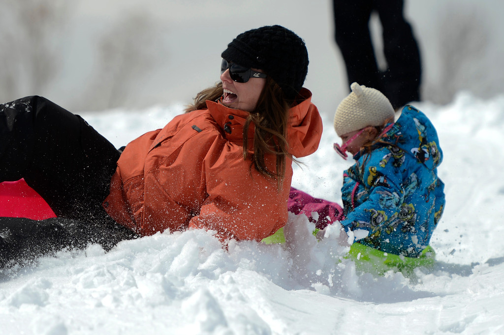 . BOULDER, CO. - APRIL 23: Janessa Berggren crashes as she and her daughter 2 year old Bailey slide down the hill at Scott Carpenter Park April 23, 2013 Boulder, Colorado. (Photo By Joe Amon/The Denver Post)