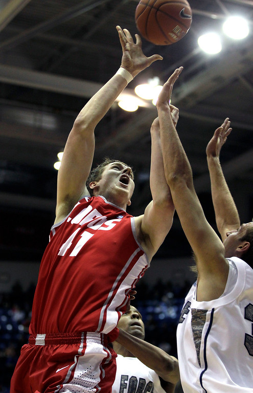 . New Mexico\'s Cameron Bairstow, left, shoots, covered by Air Force\'s Justin Hammonds, during the second half of an NCAA college basketball game at the Air Force Academy, in Colorado, Saturday March 9, 2013. (AP Photo/Brennan Linsley)