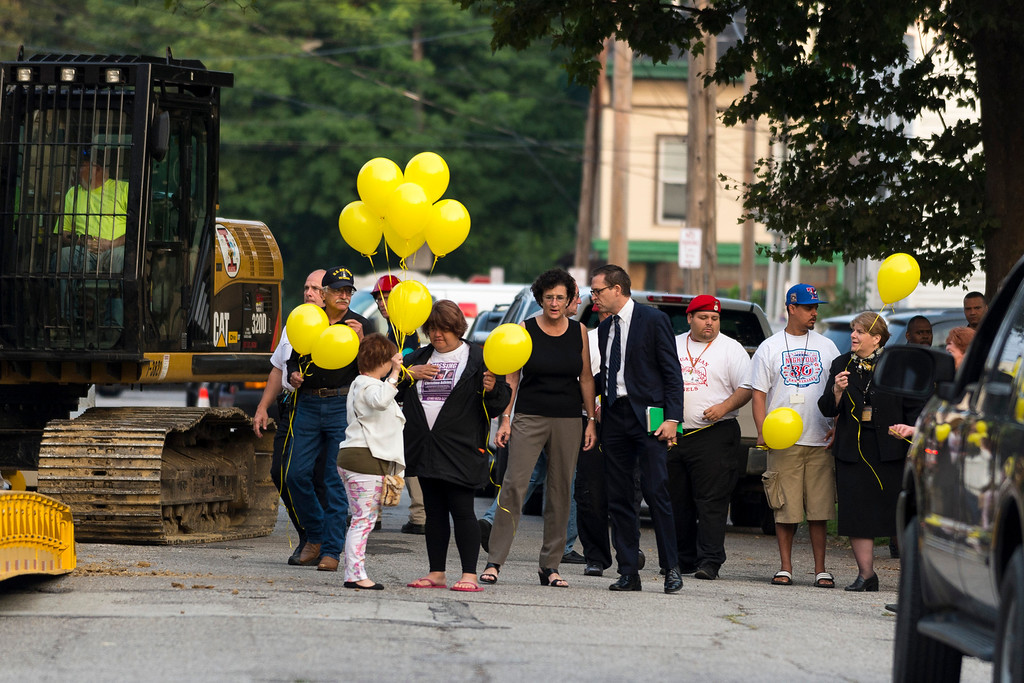 . Michelle Knight (L3) holds yellow balloons outside the home of Ariel Castro on August 7, 2013 in Cleveland, Ohio. Knight was abducted by Castro in 2002 and today the state of Ohio will demolish the home where she and two other women were held captive by Castro for over a decade. (Photo by Angelo Merendino/Getty Images)