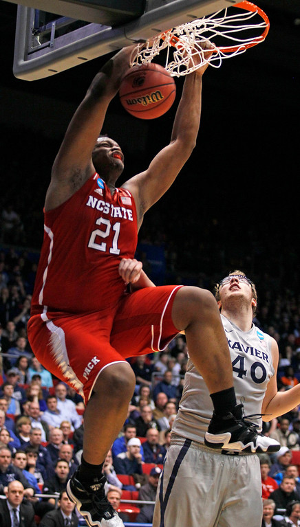 . North Carolina State forward Beejay Anya (21) dunks against Xavier center Matt Stainbrook (40) during the first half of a first-round game of the NCAA college basketball tournament, Tuesday, March 18, 2014, in Dayton, Ohio. (AP Photo/Skip Peterson)