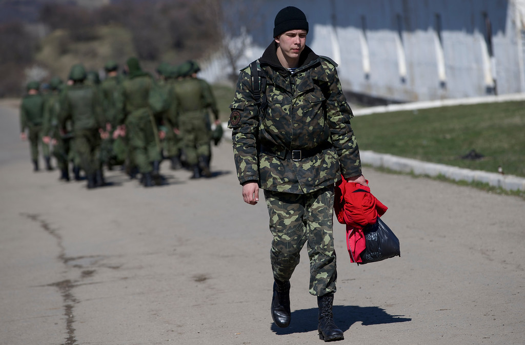 . A Ukrainian soldier walks past Russian soldiers marching to their camp outside a military base in Perevalne, Crimea, on Friday, March 21, 2014.  Russian President Vladimir Putin is expected today to sign the annexation of Ukraineís Crimean Peninsula. The upper house of the Russian parliament approved the annexation earlier today. (AP Photo/Ivan Sekretarev)