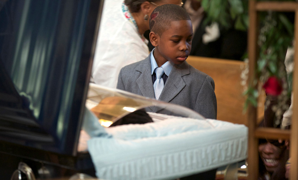 . Ronnie Chambers Jr. looks at his mother Tahitah Myles (obscured) as she collapses during the funeral for his father Ronnie Chambers, 33, a victim of gun violence, in Chicago February 4, 2013. Shirley Chambers of Chicago had four children - three boys and a girl. Now they\'re all gone. Her son, Ronnie Chambers, was the last of the single mother\'s children - all victims of gun violence in Chicago over a period of 18 years.  REUTERS/John Gress