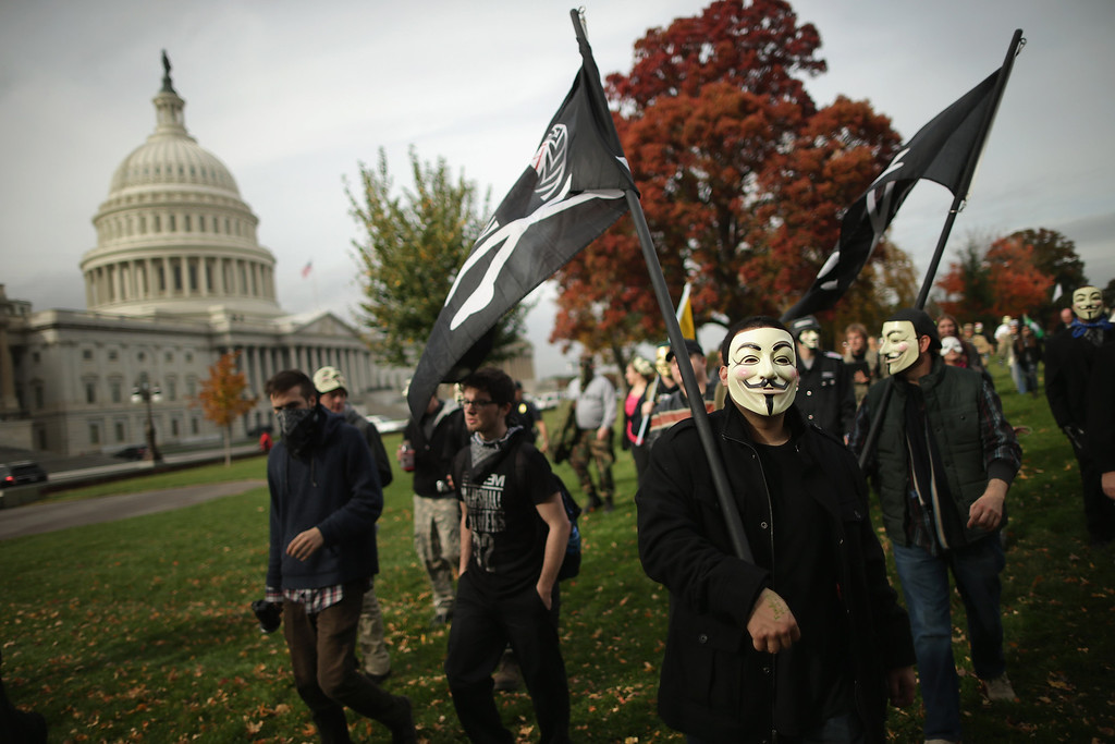 ". People march to the U.S. Captiol during the ""Million Mask March\""  November 5, 2013 in Washington, DC. Organized by members of Anonymous, WikiLeaks, The Pirate Party, Occupy Wall Street and other hacktivist movements, demonstrators marched on political landmarks and institutions around the world on Guy Fawkes Day. (Photo by Chip Somodevilla/Getty Images)"