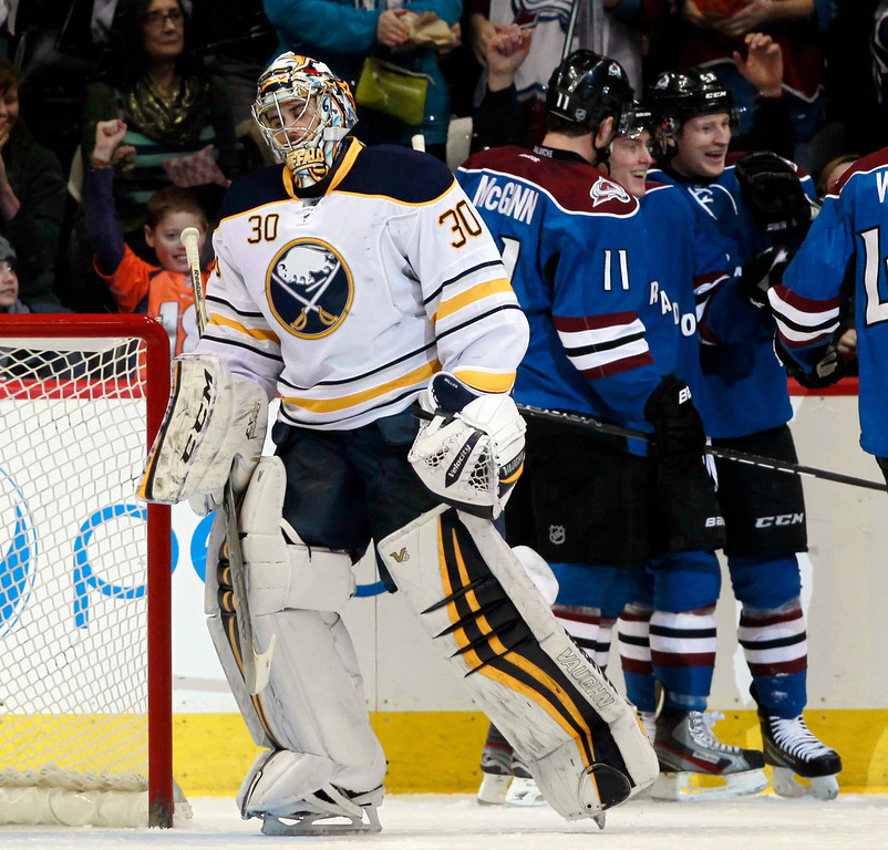 . Buffalo Sabres goalie Ryan Miller (30) reacts after giving up a goal to Colorado Avalanche defenseman Tyson Barrie, back center, as he celebrates with teammates Jamie McGinn, back left, in the first period of an NHL hockey game in Denver, Saturday, Feb. 1, 2014. (AP Photo/David Zalubowski)