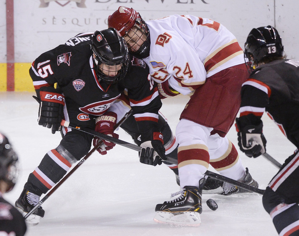 . DENVER, CO. - JANUARY 10: St. Cloud State defenseman Niklas Nevalainen (15) fought for the puck with Denver wing Evan Ritt (24) in the third period. The St. Cloud State hockey team defeated the University of Denver 6-3 at Magness Arena Friday night, January 10, 2014. Photo By Karl Gehring/The Denver Post