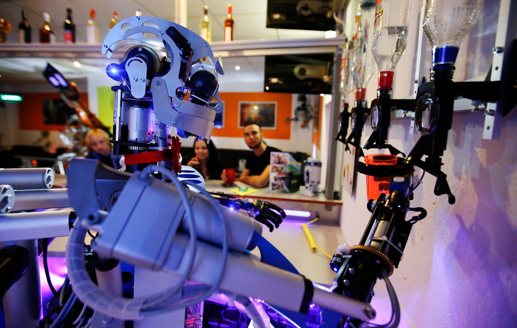 """. Humanoid robot bartender \""""Carl\"""" fills a cocktail glass with spirits to prepare a drink for a guest at the Robots Bar and Lounge in the eastern German town of Ilmenau, July 26, 2013. \""""Carl\"""", developed and built by mechatronics engineer Ben Schaefer who runs a company for humanoid robots, prepares spirits for the mixing of cocktails and is able to interact with customers in small conversations. Picture taken July 26, 2013. REUTERS/Fabrizio Bensch"""