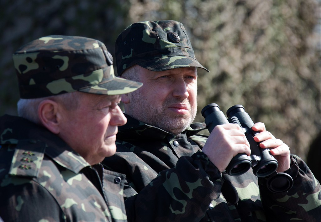 . In this photo taken Friday, March 14, 2014, acting Ukrainian President Oleksandr Turchynov, right, and Defense Minister Igor Tenyukh watch military exercises of Ukrainian troops near Chernigiv, 150 km (94 miles) north of Kiev, Ukraine. (AP Photo/Mykhailo Markiv, Pool)