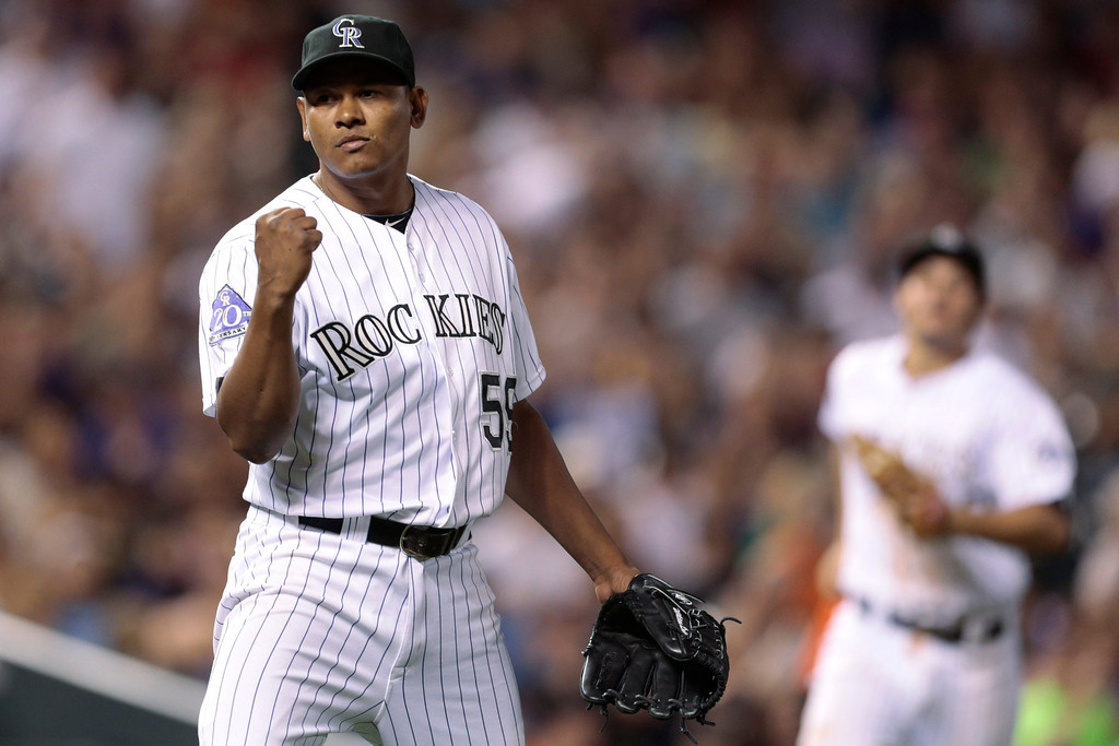 . Colorado Rockies pitcher Wilton Lopez, left, reacts to Florida Marlins batter Giancarlo Stanton (not shown) grounding out with three Marlins on-base to end the seventh inning of a baseball game in Denver, Wednesday, July 24, 2013.(AP Photo/Joe Mahoney)