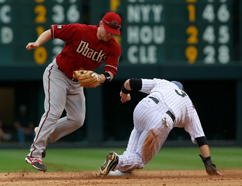 . Arizona Diamondbacks second baseman Aaron Hill, left, jumps out of the way after forcing out Colorado Rockies\' Michael Cuddyer at second base in the fifth inning of a baseball game in Denver on Sunday, Sept. 22, 2013. (AP Photo/David Zalubowski)
