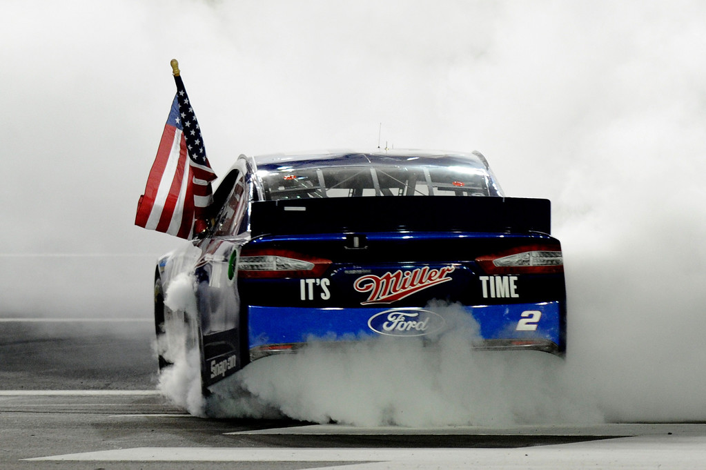 . CONCORD, NC - OCTOBER 12:  Brad Keselowski, driver of the #2 Miller Lite Ford, celebrates with a burnout after winning the NASCAR Sprint Cup Series Bank of America 500 at Charlotte Motor Speedway on October 12, 2013 in Concord, North Carolina.  (Photo by John Harrelson/Getty Images)