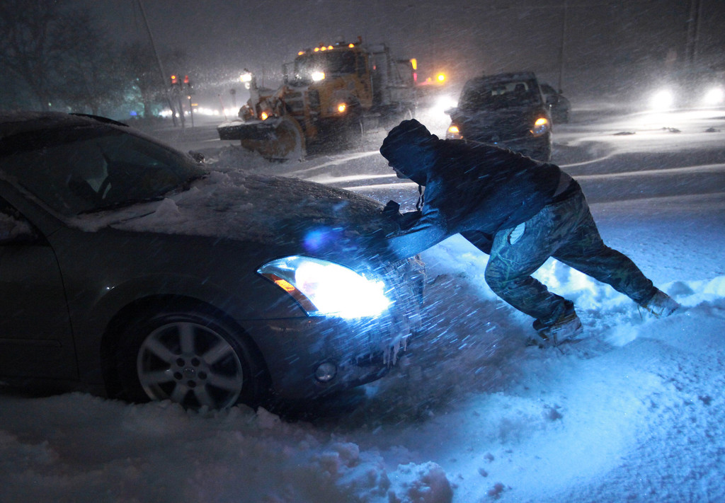 . A man tries to push a vehicle that got stuck on Route 347 in Lake Grove, N.Y. early Saturday morning, Feb, 9, 2013. Dozens of vehicles remain stranded on this stretch of Long Island road. (AP Photo/Newsday, John Paraskevas)