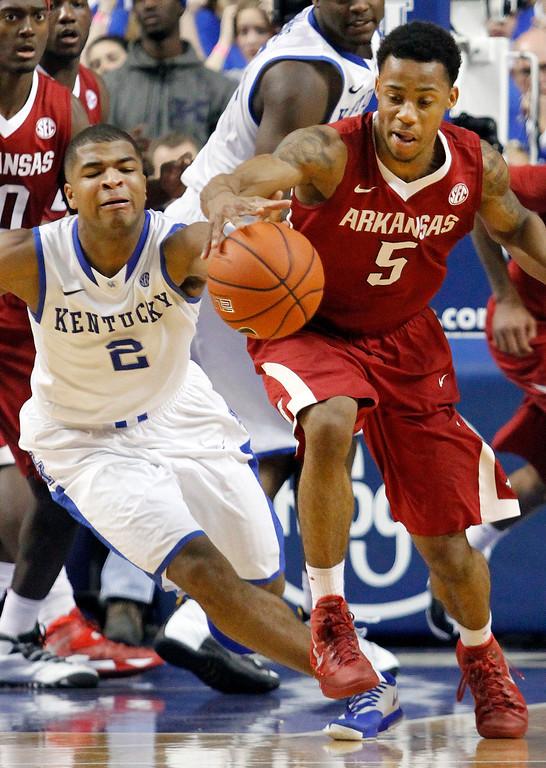 . Arkansas\' Anthlon Bell (5) and Kentucky\'s Aaron Harrison (2) chase a loose ball during overtime of an NCAA college basketball game, Thursday, Feb. 27, 2014, in Lexington, Ky. Arkansas won 71-67. (AP Photo/James Crisp)
