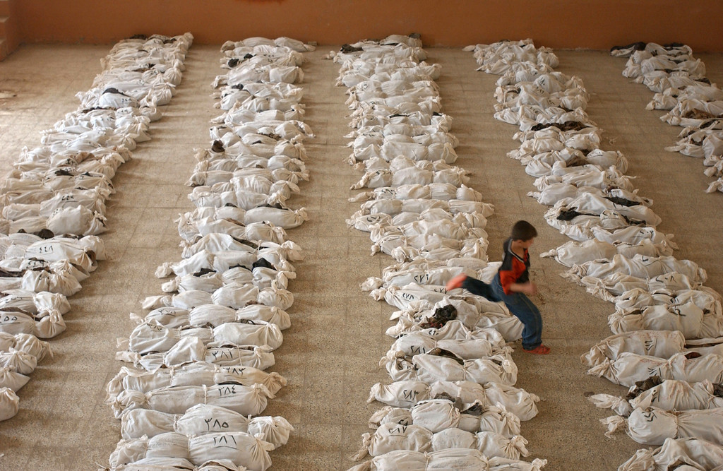 . An Iraqi child jumps over a line of remains in a school where bodies had been brought from a mass grave discovered in the desert in the outskirts of Al Musayyib, 50 km south of Baghdad, May 27, 2003 in Iraq. People had been searching for days for identity cards or other clues among the skeletons to try to find the remains of family members, including children, from the grave that locals say contained the remains of hundreds of Shi\'ite Muslims executed by Saddam Hussein\'s regime after their uprising following the 1991 Gulf War.  (Photo by Marco Di Lauro/Getty Images)