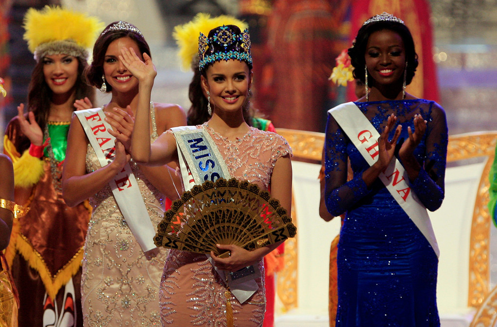 . Newly crowned Miss World Megan Young of Philippine, centre, waves, after winning the Miss World contest,  in Nusa Dua, Bali, Indonesia, Saturday, Sept. 28, 2013. (AP Photo/Firdia Lisnawati)