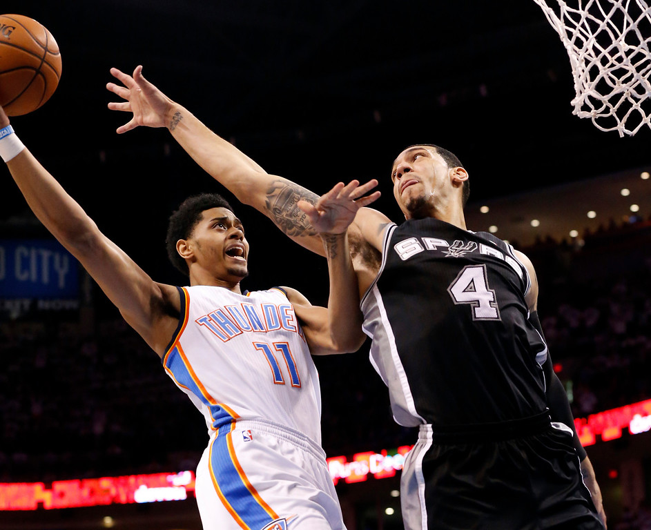 . Oklahoma City Thunder guard Jeremy Lamb (11) shoots in front of San Antonio Spurs guard Danny Green (4) in the first quarter of Game 4 of the Western Conference finals NBA basketball playoff series in Oklahoma City, Tuesday, May 27, 2014. (AP Photo/Sue Ogrocki)