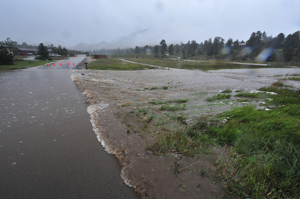 . A usually small creek overruns its banks and closes Carriage Drive on Thursday, Sept 12, 2013. The floodwaters made travel in Estes Park difficult, at best, and often dangerous. Walt Hester/Estes Park Trail-Gazette