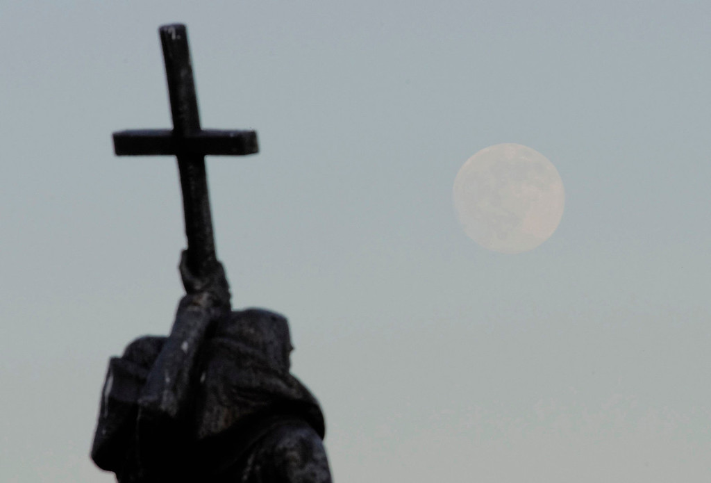 ". The moon rises over the monument of Saints Cyril and Methodius, the fathers of Slavonic literature, in the Russian far eastern city of Vladivostok on June 22, 2013. On Saturday a perigee moon will coincide with a full moon creating a ""super moon\"" when it will pass by the earth at its closest point in 2013.  REUTERS/Yuri Maltsev"
