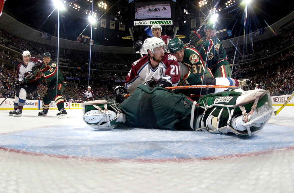 . Colorado Avalanche Peter Forsberg #21 is held down by Minnesota Wild Wes Walz #37 in front of goaltender Manny Fernandez after making a stop on forsbergs shot during the third period  in game 5 at Pepsi Center. Photo by John Leyba