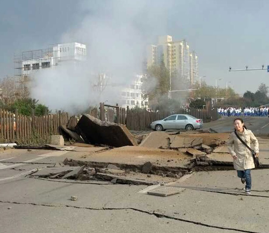 . A woman runs from the disaster scene after an explosion on an oil pipeline in Qingdao in east China\'s Shandong province 22 November 2013. At least 35 people were killed and more are injured in the morning accident.  EPA/YU Fangping