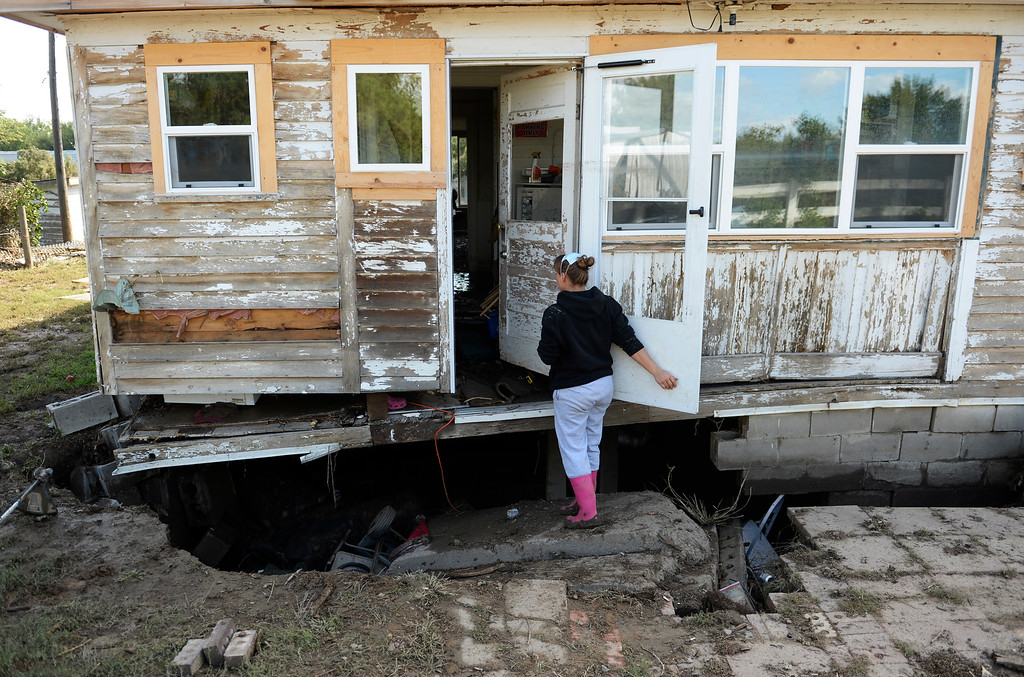. LASALLE, CO - SEPTEMBER 19: Michelle Toubeaux checks out the damage to her home in LaSalle, September 19, 2013. A folding chair is the only thing keeping up part of the home\'s  foundation. Residents start to clean up after a massive flood hit the area. (Photo By RJ Sangosti/The Denver Post)