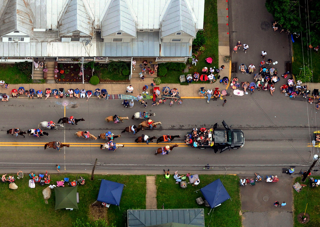 . People line North State Street while watching a group of horses and their riders participate in the Annual Millville Independence Day Parade, Thursday, July 4, 2013, in Millville, Pa. (AP Photo/Bloomsburg Press Enterprise, Jimmy May)
