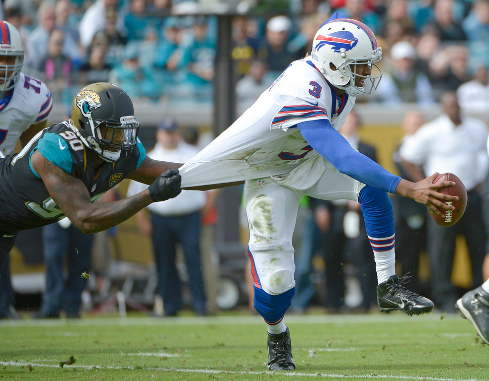 . Jacksonville Jaguars defensive end Andre Branch (90) grabs Buffalo Bills quarterback EJ Manuel (3) by the jersey to stop him during the first half of an NFL football game in Jacksonville, Fla., Sunday, Dec. 15, 2013.(AP Photo/Phelan M. Ebenhack)