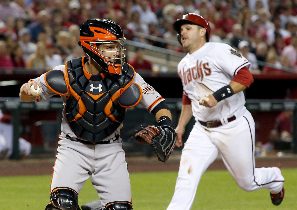 . San Francisco Giants\' Buster Posey, left, holds the baseball after he forced Arizona Diamondbacks\' Miguel Montero, right, out at home plate during the fifth inning of an opening day baseball game, Monday, March 31, 2014, in Phoenix. (AP Photo/Ross D. Franklin)