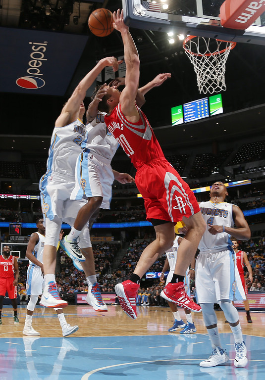 . Houston Rockets forward Donatas Motiejunas, third from left, of Lithuania, is fouled as he goes up for a shot by Denver Nuggets guard Aaron Brooks, second from left, and center Timoey Mozgov, of Russia, left, as guard Randy Foye, right, looks on in the first quarter of an NBA basketball game in Denver on Wednesday, April 9, 2014. (AP Photo/David Zalubowski)