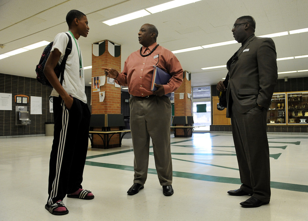 """. Michael Walker, center, an educator at Watchcare Academy, and Randy McCowan, right, publisher of the \""""Body of Christ\"""" newspaper, talk to Jeremiah Wright-Graham, left, a senior at George Washington High School, before Black Men in Support of Education, a group of successful black men who mentor kids, sat on a panel and spoke to students at the school on March 26 in Denver, Colo. Photo by Jamie Cotten, Special to The Denver Post"""