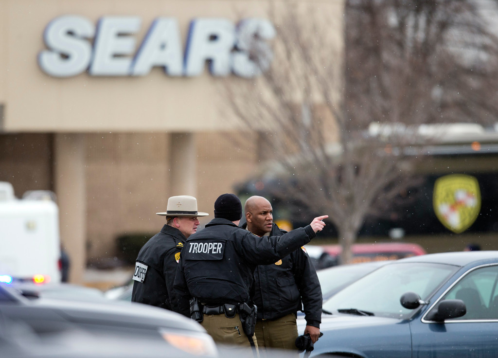 . Police talk in a parking lot outside a Sears store after a shooting at The Mall in Columbia on Saturday, Jan. 25, 2014 in Columbia, Md. Police say three people died in a shooting at the mall in suburban Baltimore, including the presumed gunman.(AP Photo/ Evan Vucci)