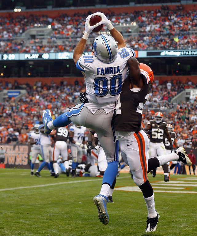 . Tight end Joseph Fauria #00 of the Detroit Lions catches a touchdown pass over defensive back T.J. Ward #43 of the Cleveland Browns at FirstEnergy Stadium on October 13, 2013 in Cleveland, Ohio.  (Photo by Matt Sullivan/Getty Images)