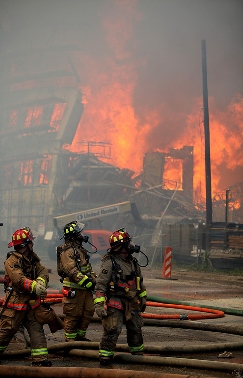 . Houston firefighters see a second building catch fire as they attempt to contain a five-alarm fire at a construction site Tuesday, March 25, 2014, in Houston.  (AP Photo/Houston Chronicle, Mayra Beltran)