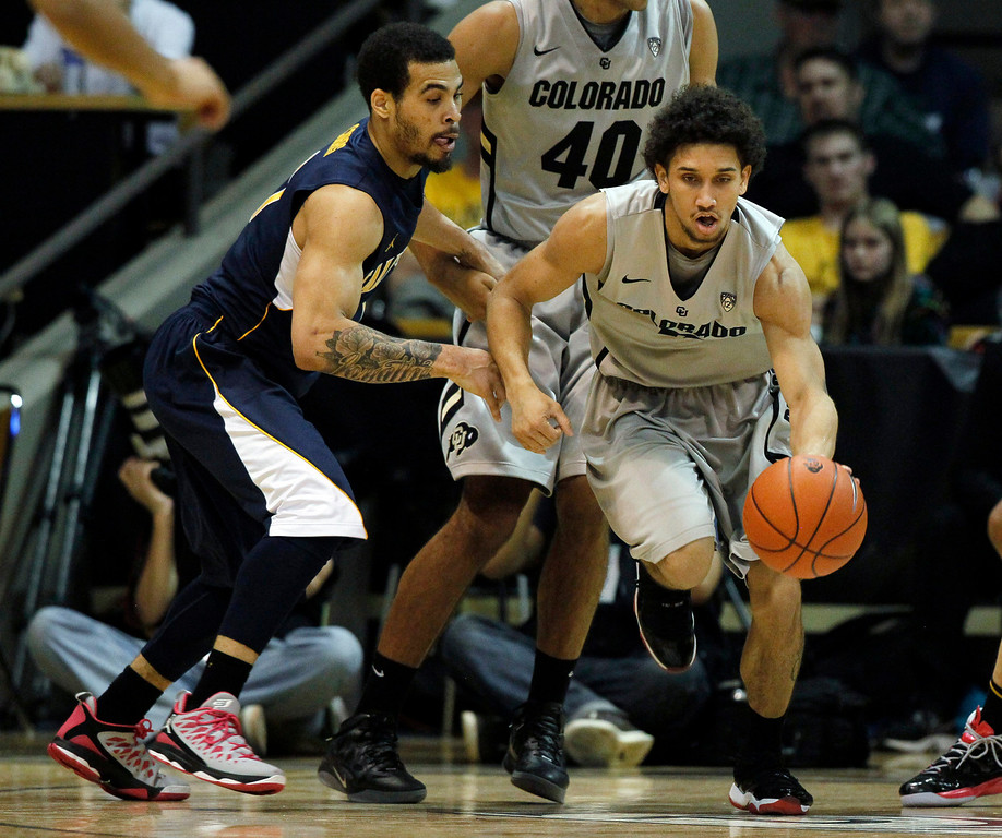 . Colorado guard Askia Booker, right, picks up a loose ball in front of California guard Justin Cobbs in the second half of Colorado\'s 81-71 victory in an NCAA basketball game in Boulder, Colo., Sunday, Jan. 27, 2013. (AP Photo/David Zalubowski)
