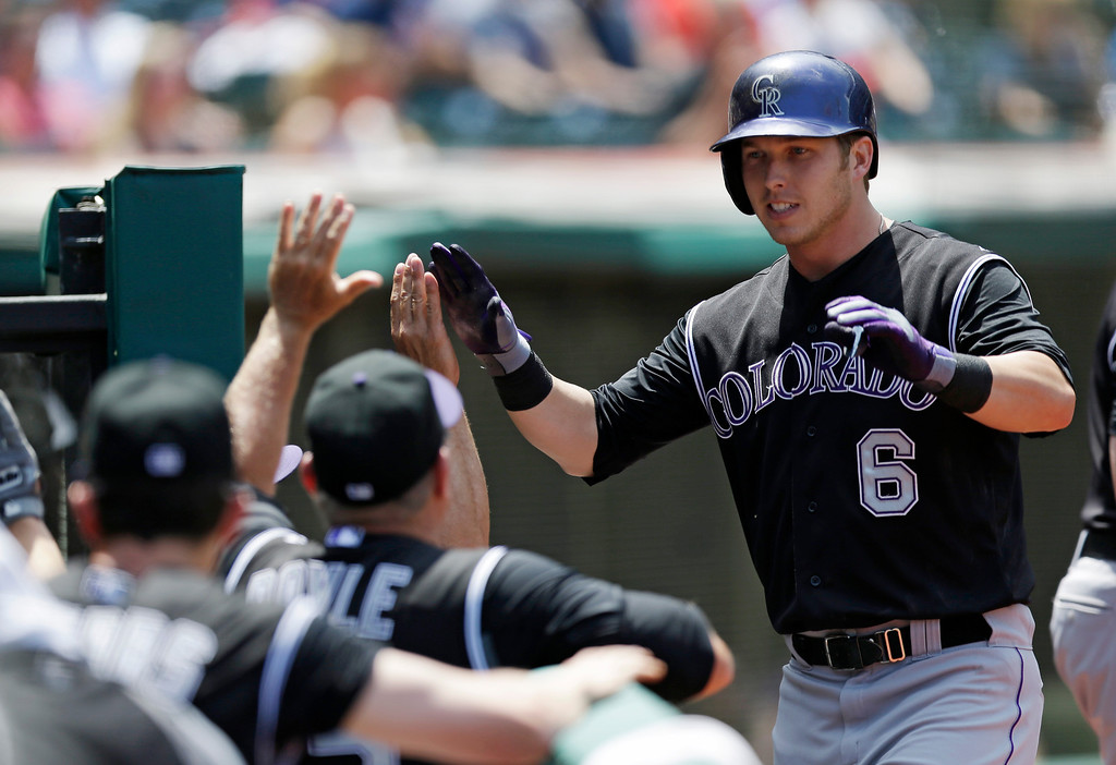 . Colorado Rockies\' Corey Dickerson (6) is congratulated by teammates after hitting a two-run home run off Cleveland Indians starting pitcher Josh Tomlin in the second inning of a baseball game on Sunday, June 1, 2014, in Cleveland. Rockies\' Justin Morneau also scored. (AP Photo/Tony Dejak)