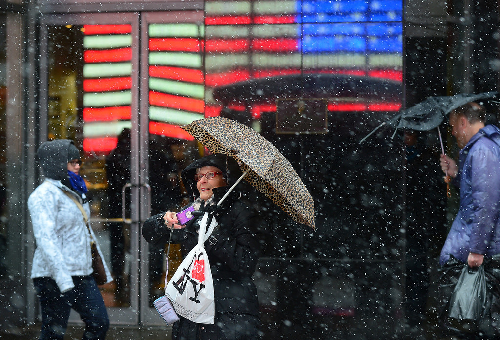 . A woman gets ready to take a picture as snow falls over Times Square in New York, March 8, 2013. AFP PHOTO/EMMANUEL DUNAND/AFP/Getty Images