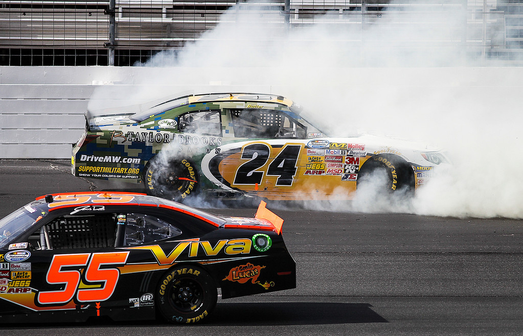 . Jamie Dick passes safely as Brett Butler spins out and hits the wall during the NASCAR Nationwide Series auto race at New Hampshire Motor Speedway in Loudon, N.H., Saturday, July 13, 2013.  (AP Photo/Cheryl Senter)