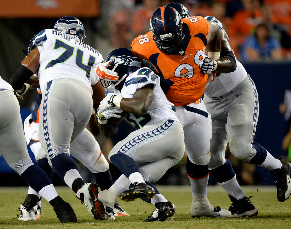 . Defensive tackle Terrance Knighton (98) of the Denver Broncos wraps up running back Christine Michael (33) of the Seattle Seahawks during the second quarter.  The Denver Broncos vs the Seattle Seahawks At Sports Authority Field at Mile High. (Photo by John Leyba/The Denver Post)
