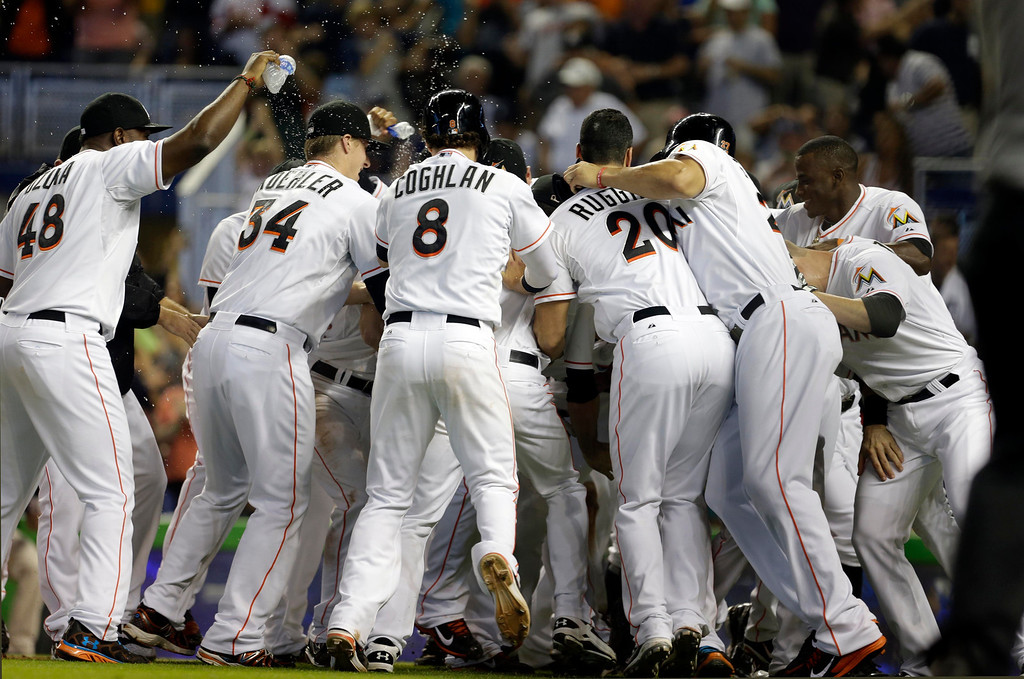 . Miami Marlins\' Henderson Alvarez, not seen, is mobbed by teammates as they celebrate a 1-0 no-hitter win against the Detroit Tigers after an interleague  baseball game, Sunday, Sept. 29, 2013, in Miami. . (AP Photo/Alan Diaz)