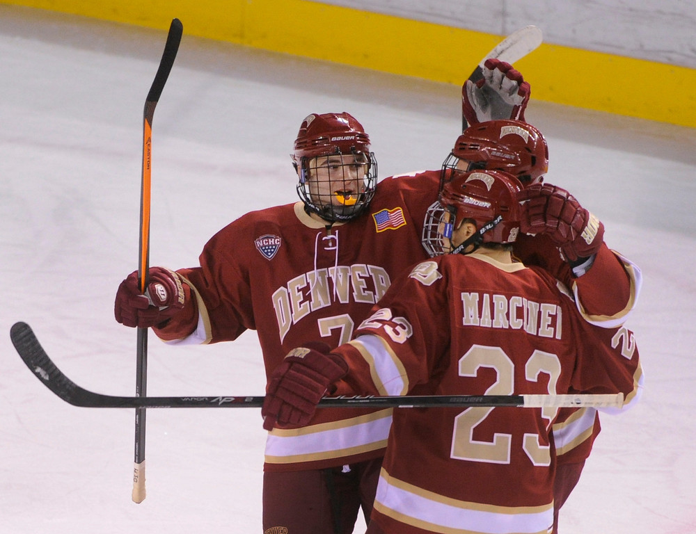. DENVER, CO. - OCTOBER 25: Denver defenseman Will Butcher (7) and center Matt Marcinew (23) helped David Makowski (10) celebrate his power play goal in the first period. The University of Denver hockey team hosted Niagara at Magness Arena Friday night, October 25, 2013. Photo By Karl Gehring/The Denver Post